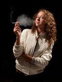 Beautiful woman standing and smoking — Stock Photo