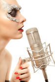 Woman in foil mask with microphone — Stock Photo
