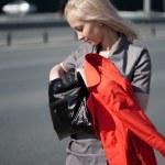 Woman walking and looking to her handbag — Stock Photo
