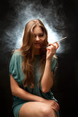 Beautiful woman with full lips sitting and smoking — Stock Photo