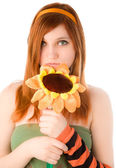 Red haired girl holding big smiling flower — Stock Photo