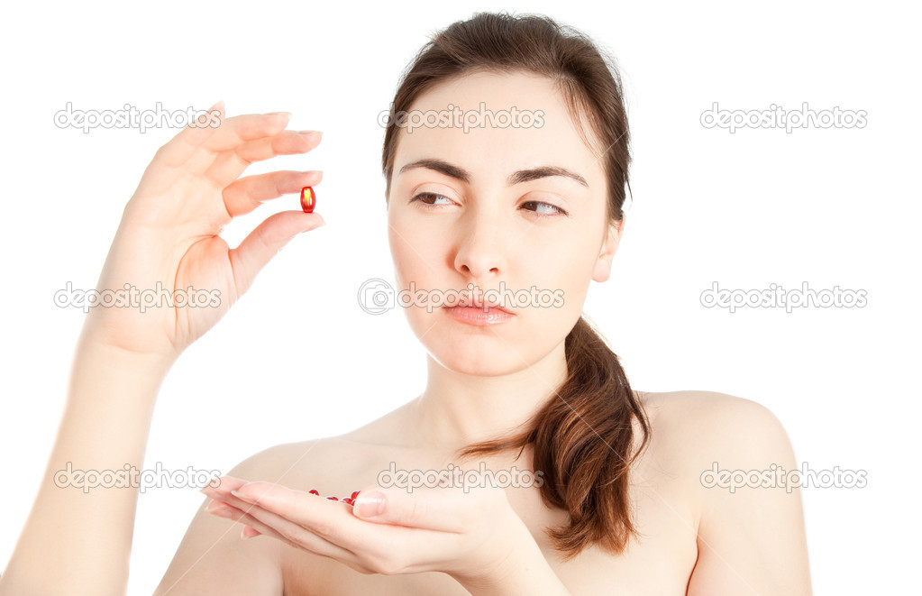 Beautiful woman looking doubtly on the pill isolated on white — Stock Photo #8494414