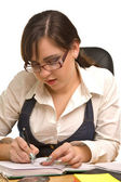 Young businesswoman in glasses writing — Stock Photo