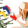 Woman dressing christmas tree — Stock Photo #8640797