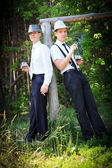 Handsome gangsters smoking and drinking in the forest — Stock Photo