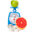 A piece of grapefruit, an apple, measure tape and scale — Stock Photo #8780134