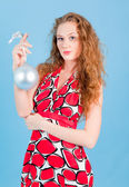 Beautiful woman in red dress smiling with silver new year ball — Stock Photo
