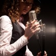 Beautiful singer in hat with microphone — Stock Photo #8881810