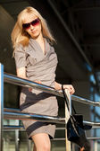 Dükkanın yanında gri elbiseli kadın — Stok fotoğraf