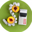 Stock Photo: Concept of counting calories (peach, calculator and tape measur