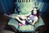 Sexig kvinna sitter på fåtöljen — Stockfoto