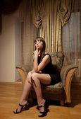 Sexy žena v černých šatech sedící — Stock fotografie