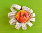 Picture of a peach and tape measure — Stock Photo