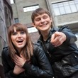 Photo of smiling woman and man pointing his finger to the camera — Stock Photo #9110730