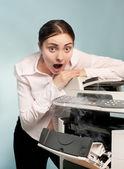 Surprised woman with smoking copier — Stock Photo