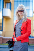 Beautiful woman in red jacket walking — Stock Photo