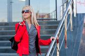 Vrouw in rood jasje staande op de winkel — Stockfoto