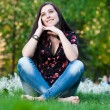 Happy pretty girl sitting on the grass — Stock Photo #10453472