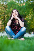 Happy pretty girl sitting on the grass — Stock Photo
