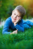Cheerful little kid laying on the grass — Stock Photo