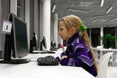 Computador de uso pequena garota em uma biblioteca — Foto Stock