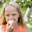 Five-year-old girl eating apple - Stockfoto