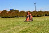 Mature man driving grass cutter — Stock Photo