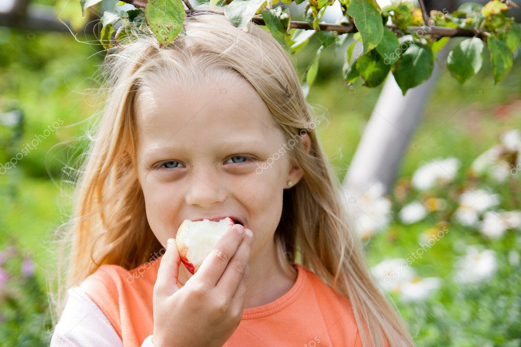 Happy little girl holding apple in her hands — Stock Photo #8404807