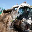 Mini excavator at construction site - Stock Photo