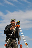 Theodolite on a tripod with construction worker — Stock Photo