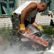 Worker with industrial saw cutting a concrete block — Stock Photo