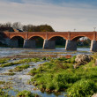 Old brick bridge over river Venta — Stock Photo