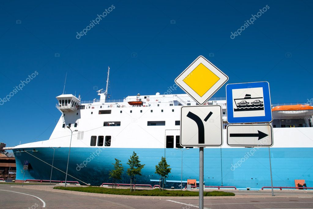 Sign entry to the ferry port with a ferry in the background — Stock Photo #9869822