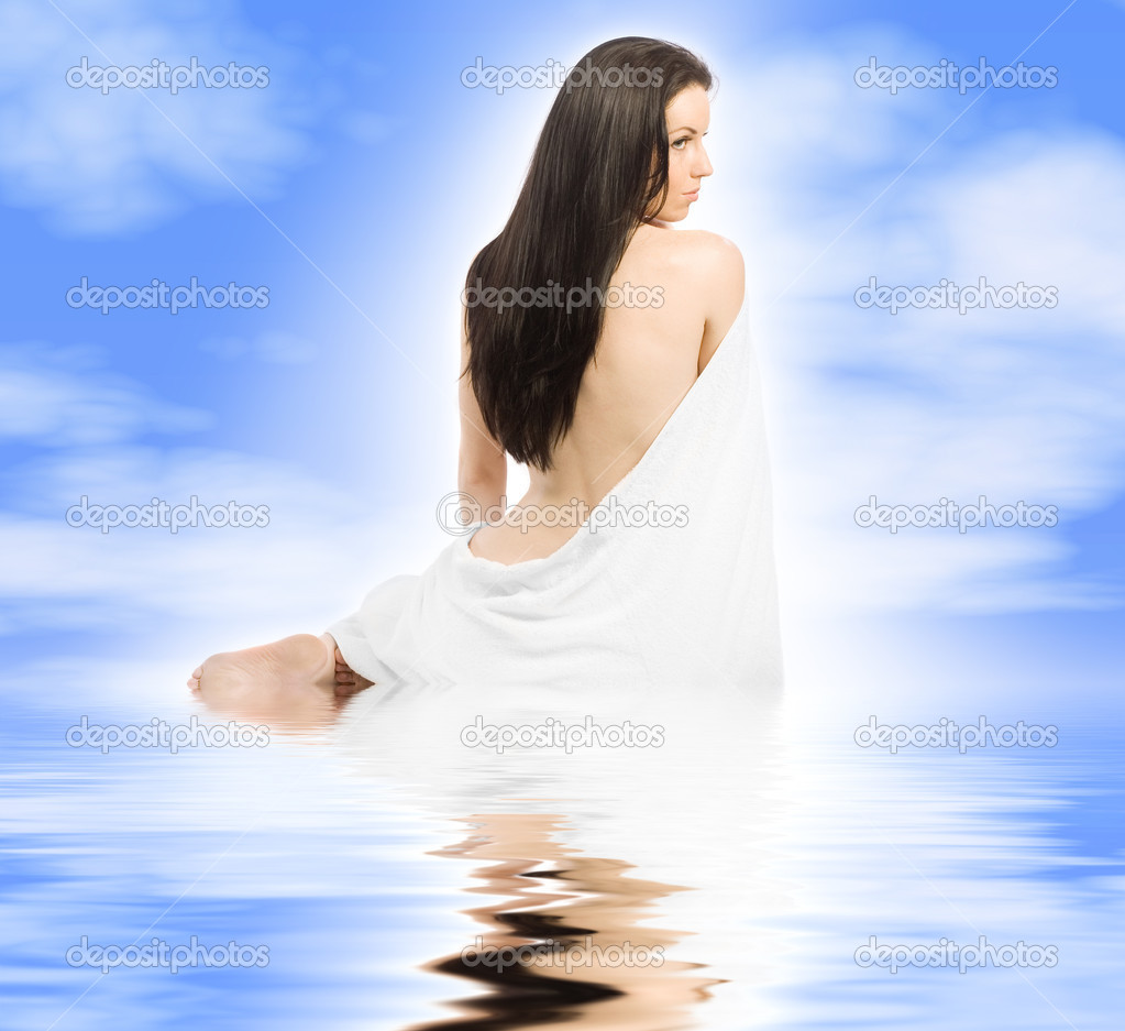 Beauty sits with towel blue sky with reflective water — Stock Photo #10541231