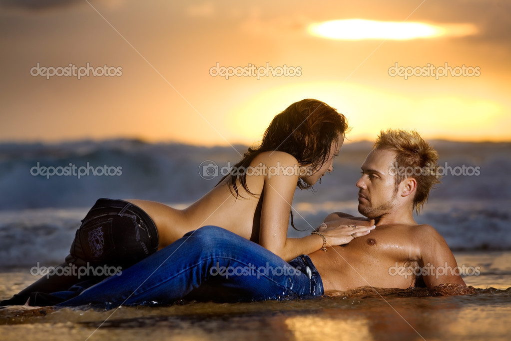 Young sexy couple on beach topless in jeans — Stock Photo #8147513