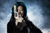 Asian beauty holding gun with smoke — Stock Photo