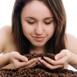 Beautiful young woman smelling coffee beans — Stock Photo