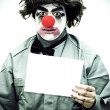 Unhappy Clown Holding Sign - Stock Photo