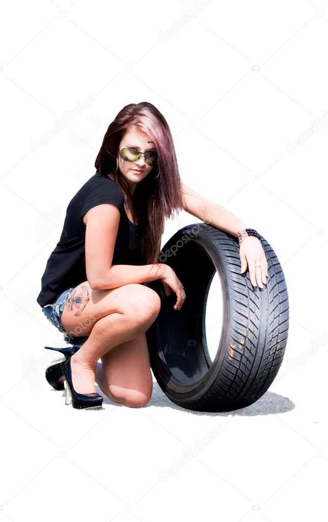 Attractive Female Brunette Babe In Sunglasses Kneeling Down Holding A Tyre Or Tire In A Sports Car Race Or Racing Concept, Image Isolated On White Background — Stock Photo #10037810