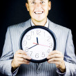 Smiling man in suit, holding clock - Stock Photo
