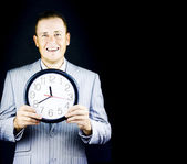 Smiling man in gray suit holding a clock — Stock Photo