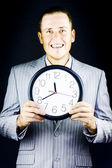 Smiling man in suit, holding clock — Stock Photo