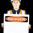 Man with construction helmet holding 'danger' sign — Photo