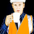 Man with construction helmet and white cup - Stock Photo
