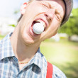 Man Catches Golf Ball In Mouth - Stock Photo