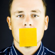 Man with blank paper note over his mouth — Stock Photo