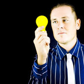 Young man holding yellow bulb in his hand — Stock Photo