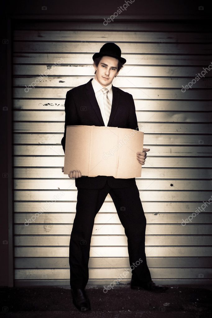 Full Body Portrait Of A Well Dressed Vintage Man Wearing Bowler Hat And Suit Holding A Blank Cardboard Sign In Front Of A Garage Door In A Limo Driver Concept — Stock Photo #10155467