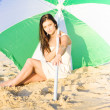 Woman Sitting On Beach With Umbrella Or Parasol — Stockfoto
