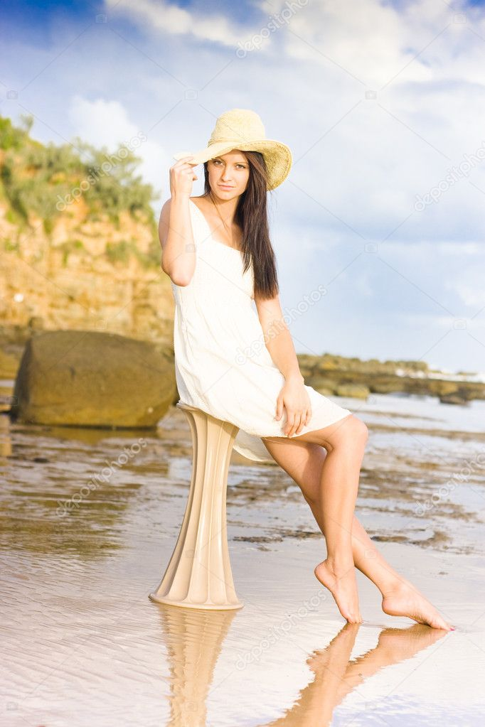 Fashion Shot Of A Beautiful Woman At The Beach Sitting On A Greek Style Pillar. White Sand Blue Cloudy Sky — Stock Photo #10220644